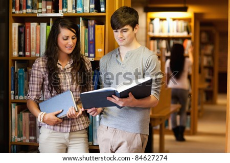 Smart students reading a book in a library