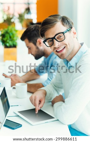 Smart technologies make life easier. Cheerful young man working on digital tablet and looking at camera while man holding mobile phone in the background  - stock photo