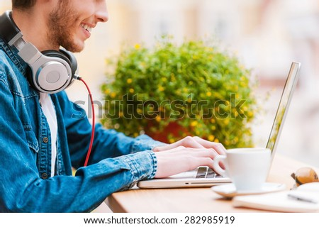 Smart technology for perfect style. Cropped image of smiling young man working on laptop while sitting at sidewalk cafe - stock photo