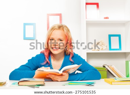 Smart teen girl with books and textbooks on table - stock photo