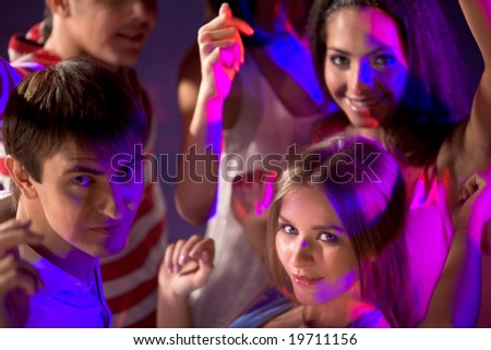 Smart teenagers looking at camera while dancing at disco - stock photo