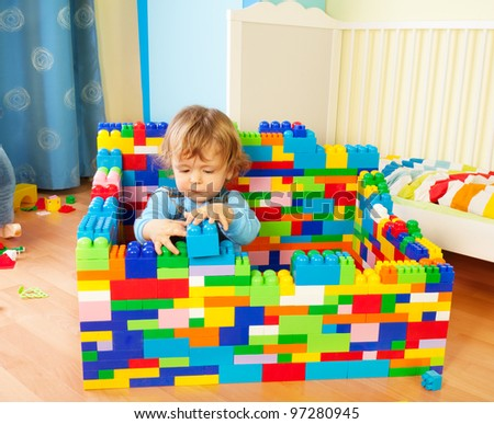 Smart toddler building a castle of toy plastic blocks - stock photo