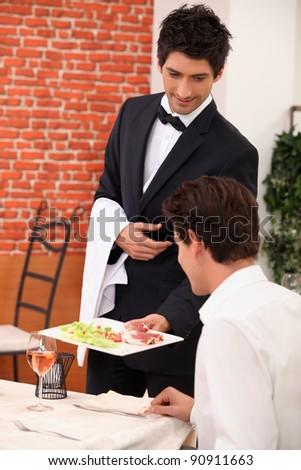 Smart waiter in restaurant - stock photo