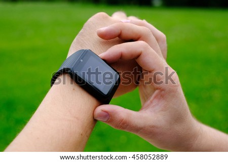Smart watch with blank screen outdoors on green background