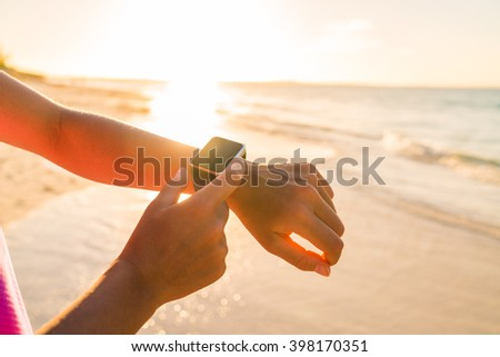 Smart watch woman using smartwatch touching button and touchscreen on active sports activity or morning jogging during beach sunrise or sunset. Closeup of hands and wrist with smart watch screen. - stock photo