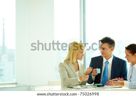 Smart woman explaining her idea to colleagues in office - stock photo