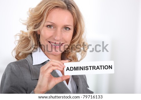 Smart woman holding a sign entitled 'ADMINISTRATION' - stock photo