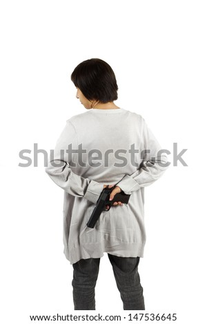 Smart woman put the gun behind her back. Isolated against white background.