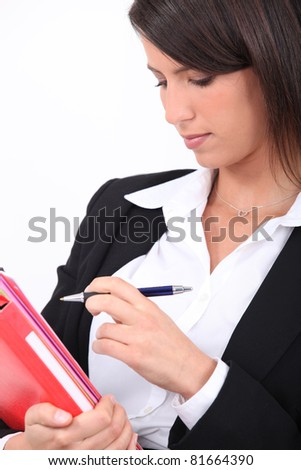 Smart woman ticking something off a file - stock photo