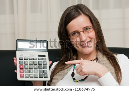 Smart woman working on a laptop in her living room and pointing to the calculator - stock photo