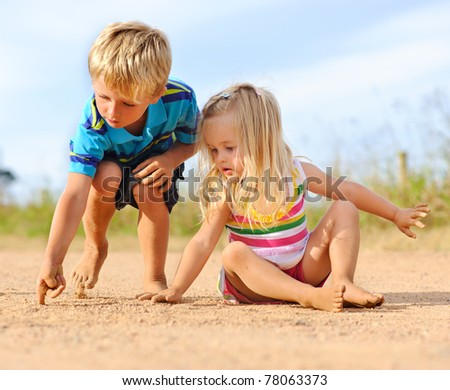 Smart young boy points out the word he wrote in the sand to his cute sister