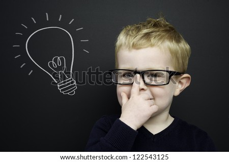 Smart young boy wearing a navy blue jumper and glasses stood in front of a blackboard with a drawn on chalk light bulb