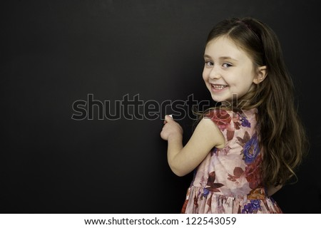 Smart young girl wearing a red dress writing on a blackboard - stock photo