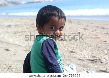 smart young happy indian boy with big eyes sitting at a beach turning back and smiling on a bright beautiful sunny day with calm blue waves in the background - stock photo