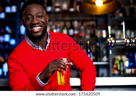 Smart young man drinking beer in nightclub - stock photo