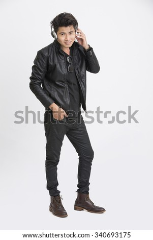 Smart young man in urban style listening music in headphone on white. - stock photo