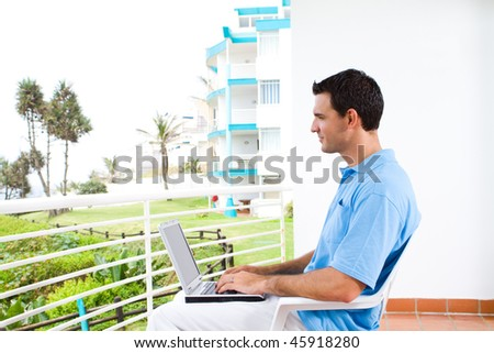 smart young man using laptop on balcony with sea view behind - stock photo