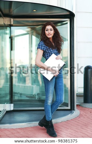 Smart young woman leaving an office building through revolving glass doors - stock photo