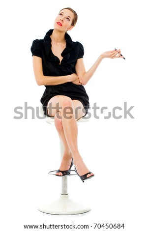 smart young woman sitting on a stool holding a cellphone on white background - stock photo