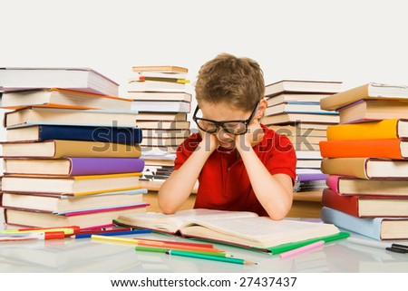 Smart youth in eyeglasses looking into open book before him - stock photo