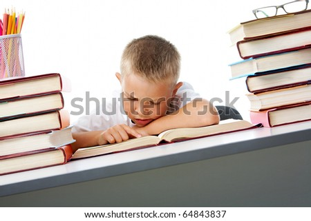 Smart youth reading open book before him with serious facial expression - stock photo
