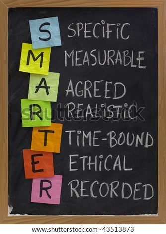 SMARTER (specific, measurable, agreed, realistic, time-bound, ethical, recorded) - acronym for goal setting approach, white chalk handwriting, colorful sticky notes on blackboard - stock photo