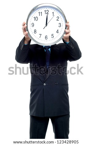 Smartly dressed businessman holding wall clock in front of his face.