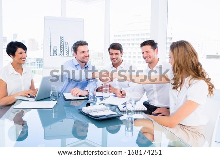 Smartly dressed executives shaking hands during a business meeting in the office - stock photo