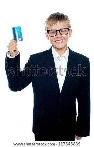 Smartly dressed young boy standing in front of the camera showing off his cash card - stock photo