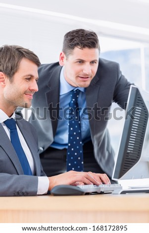 Smartly dressed young businessmen using computer at office desk