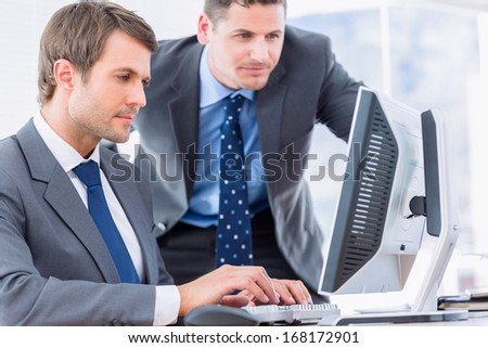 Smartly dressed young businessmen using computer at office desk - stock photo