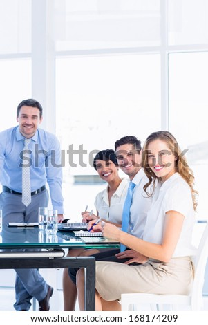 Smartly dressed young executives around conference table in office - stock photo