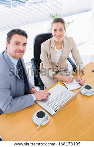 Smartly dressed young man and woman in a business meeting at office desk