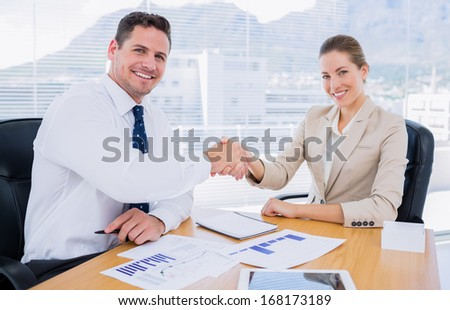 Smartly dressed young man and woman shaking hands in a business meeting at office desk - stock photo