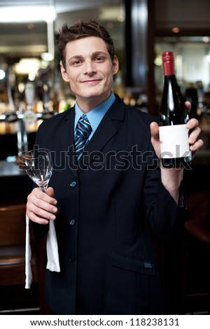 Smartly dressed young man showing you the alcohol bottle. Time to relax and enjoy...cheers - stock photo
