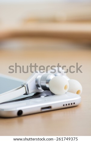 Smartphone and earphones on table.  Focus on earphones. - stock photo