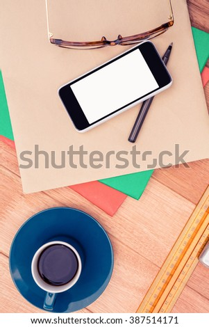 Smartphone and eye glasses on paper by coffee cup at table in office - stock photo