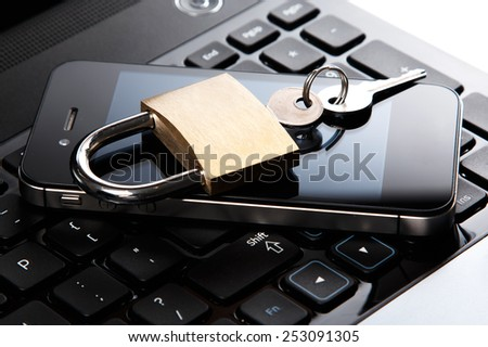 Smartphone and padlock is lying on a laptop keyboard - stock photo