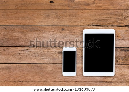 Smartphone and tablet with black screen on old wooden background - stock photo