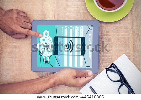 Smartphone apps icons against cropped image of hand using on digital tablet - stock photo