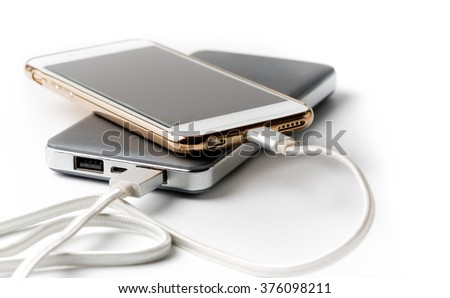 Smartphone charging with power bank on white background - stock photo