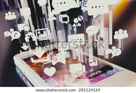 Smartphone emitting holographic social media icons. - stock photo