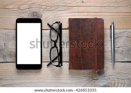 Smartphone, glasses, diary and pen on wooden table top view - stock photo