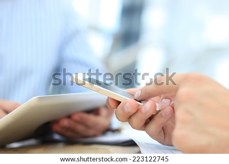 Smartphone handheld in closeup, colleagues working in background