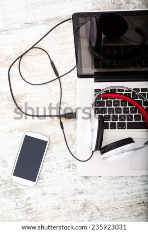 Smartphone, Headphones and Laptop on a wooden Desktop.  - stock photo