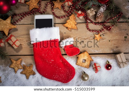 Smartphone in a Christmas sock on wood