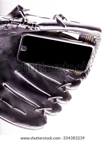 Smartphone in baseball glove, over white background, vertical image - stock photo