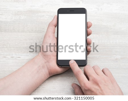 Smartphone in hand, closeup on a light table - stock photo