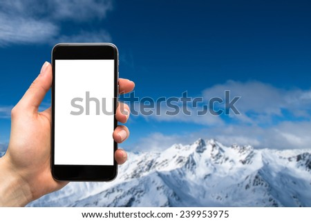 smartphone in the hands of women and the mountains in winter - stock photo