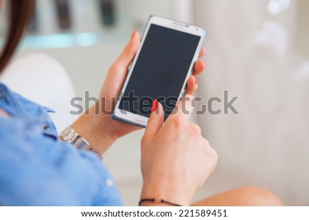 Smartphone in woman's hands. Inside photo